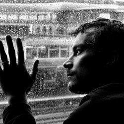 Мужчина грустящий у окна. За окном дождь