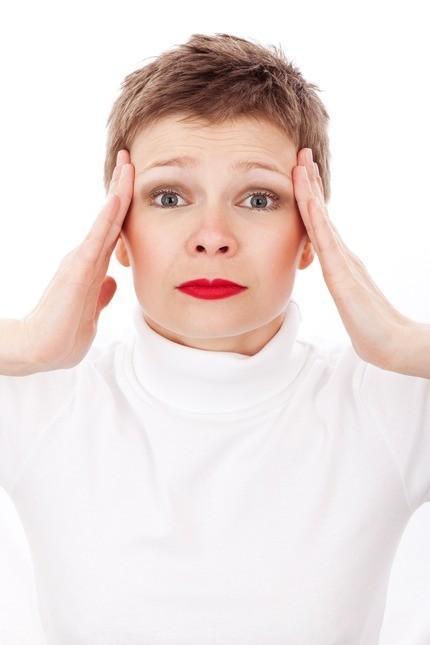 женщина корчится в муках от головной боли